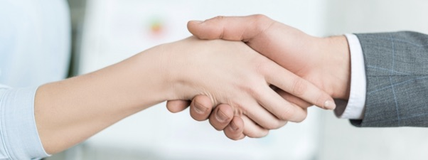 A business woman shaking hands with a business man agreeing on SEO services.