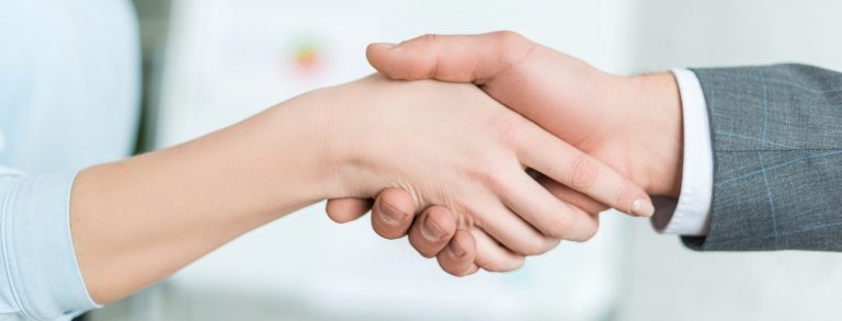 A business man shaking hands with a business woman to start SEO services to rank his website on Page 1 of Google
